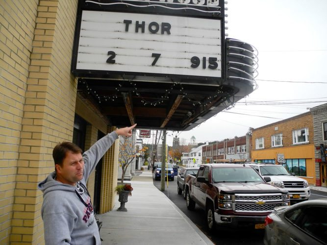 """Cory Hanf points to the Hollywood Theater's marquee in downtown AuSable Forks. The Hollywood was one of the North Country theaters saved through the """"Go Digital or Go Dark"""" campaign, developed by the Adirondack North Country Association, the Adirondack Film Society and Sierra Hanf, Cory's wife. (Enterprise photo — Aaron Cerbone)"""