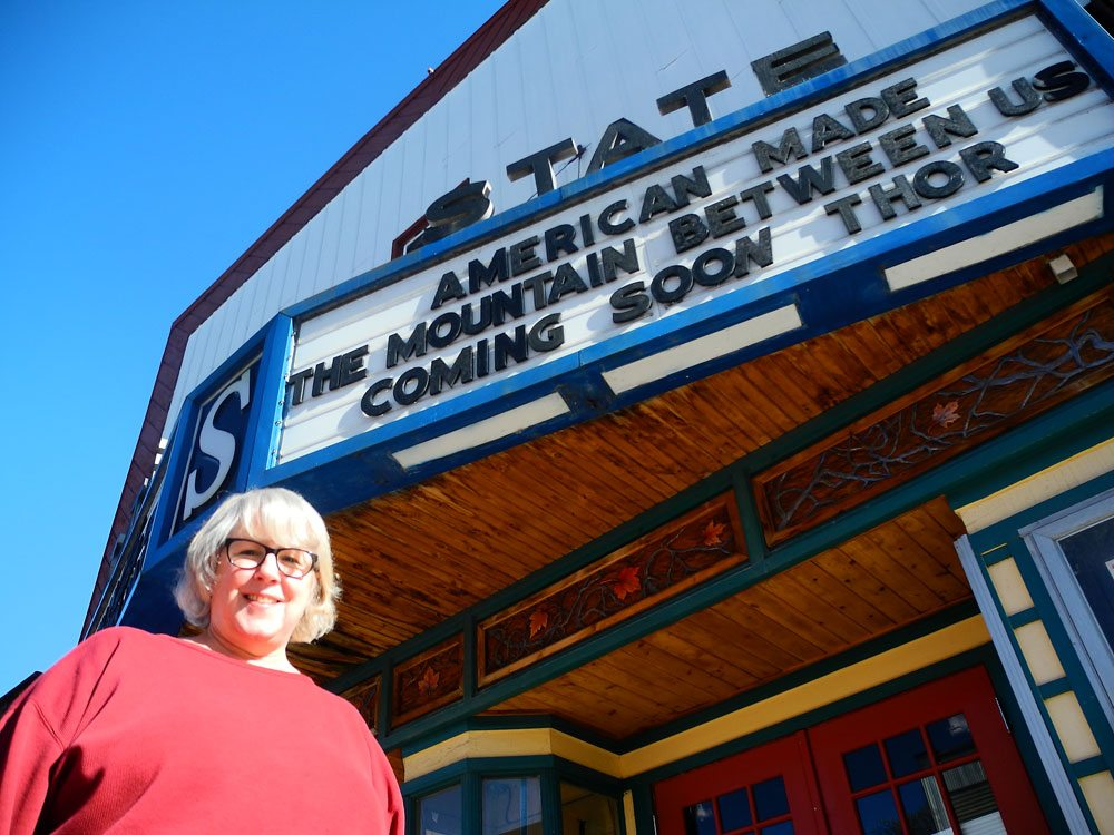 Sally Strasser stands in front of the State Theater's marquee on Park Street in Tupper Lake. Strasser said she saves money on a booking agent by booking films herself, using her contacts and knowledge from years in the film business. (Enterprise photo — Aaron Cerbone)