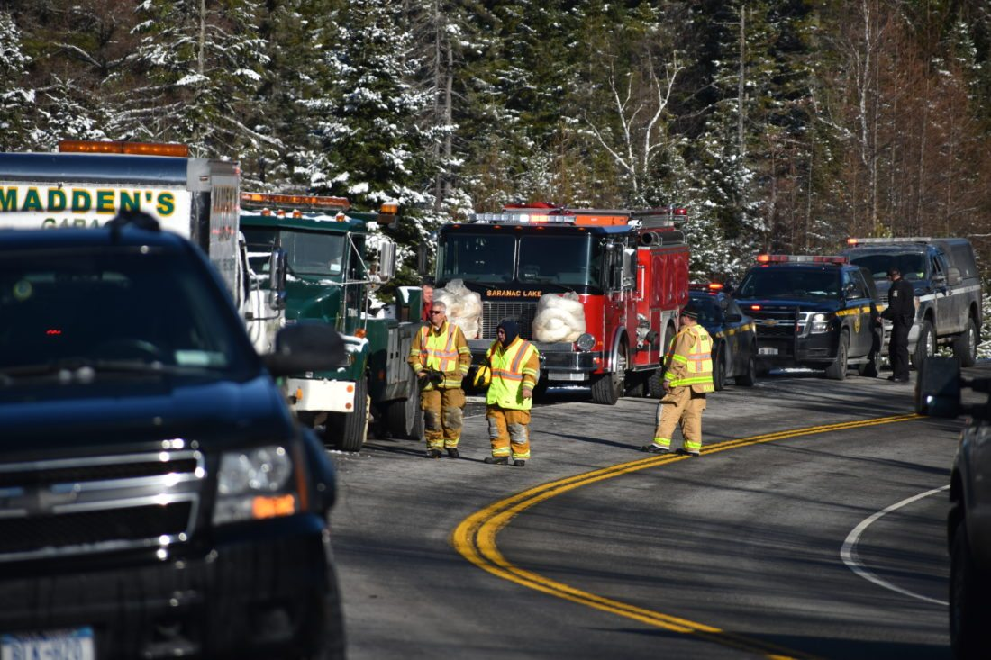 Emergency service crews respond to an overturned tractor-trailer on state Route 3 between Saranac Lake and Tupper Lake Tuesday morning. The road was closed for several hours while debris was cleaned up. (Enterprise photo — Griffin Kelly)