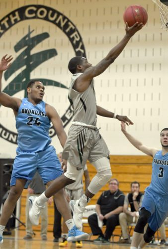 North Country's Devonte Walker glides toward the basket past Onondaga's Shemere Elliot for a second-half layup during Tuesday's game in Saranac Lake. (Enterprise photo — Lou Reuter)