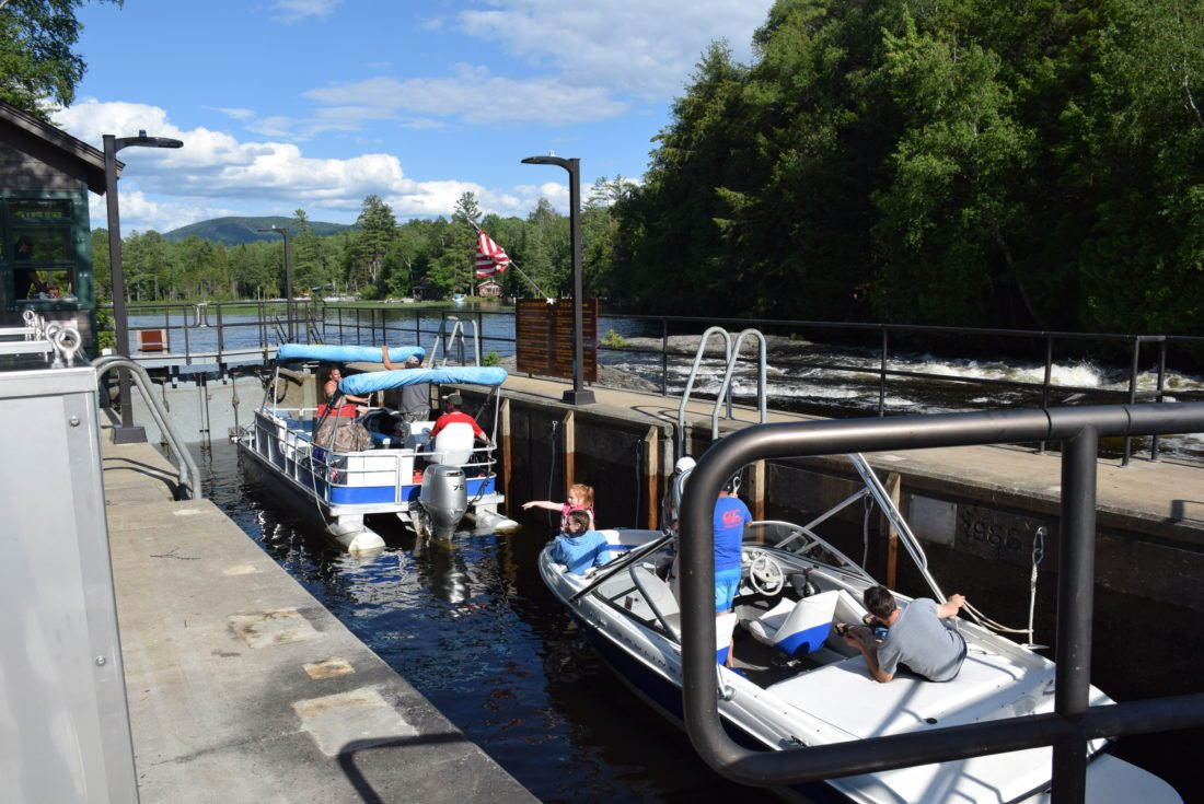 Two boats make their way through the Lower Locks during the Fourth of July holiday this past summer. The locks will be closed starting Monday and will reopen after ice-out in the spring. (Enterprise photo — Justin A. Levine)