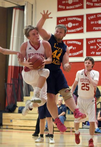 Saranac Lake's Jarrett Ashton drives in for a layup while Logan Brown defends for Lake Placid during Wednesday's non-league game. Ashton finished as the game's top scorer with 25 points. (Enterprise photo — Lou Reuter)