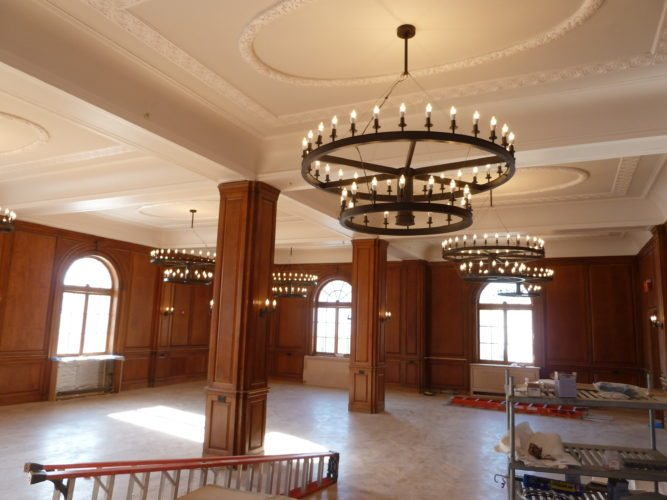 The Hotel Saranac ballroom is seen Tuesday with new chandeliers, restored oak wall paneling and — revealed underneath the old carpeting — a herringbone-pattern wood floor. (Enterprise photo — Peter Crowley)