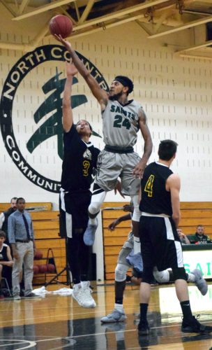 North Country sophomore Malik Wilkinson soars toward the basket over Paul Smith's players Nick Fraser (4) and Shane Stone (3) during the Saints' win Thursday night. (Enterprise photo — Justin A. Levine)