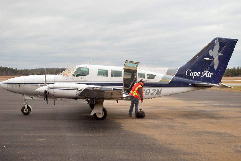 A Cape Air employee loads one of the airline's Cessna passenger planes at the Adirondack Regional Airport in Lake Clear. (Enterprise photo — Chris Knight)