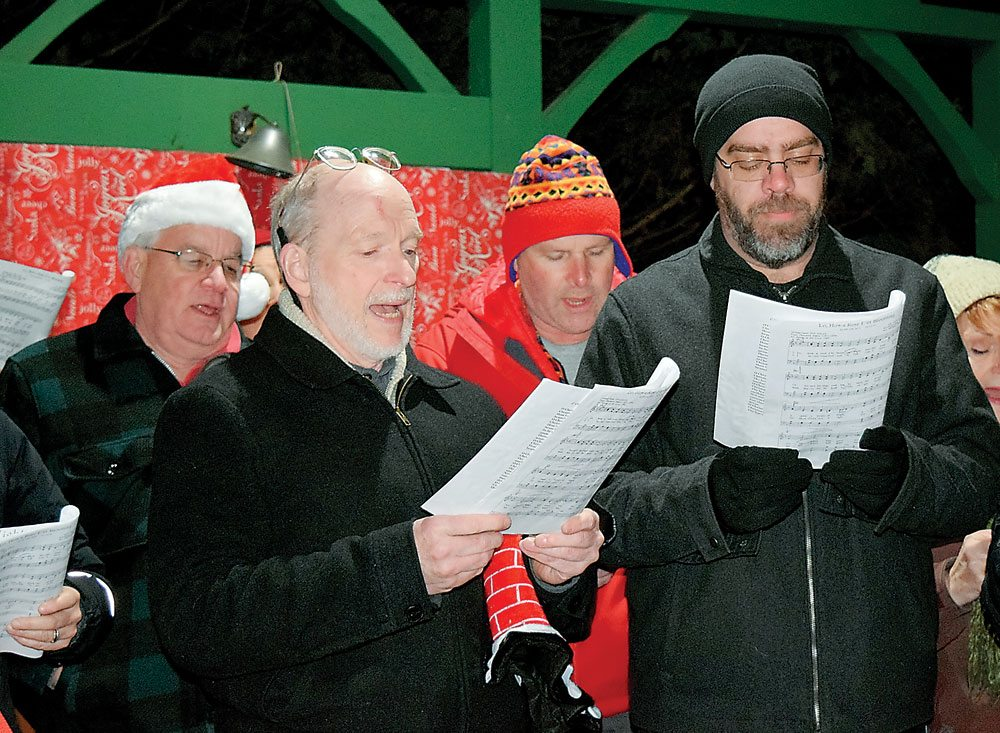 The Northern Lights Choir sings Christmas carols at Friday's Tree Lighting Ceremony in Saranac Lake. From left are Lonnie Ford, Dr. Tony Waickman, Milt Adams and Rick Burdt. The choir will perform its Winter Concert at 8 p.m. Friday, Dec. 8 at St. Bernard's Church in Saranac Lake. (Enterprise photo — Glynis Hart)