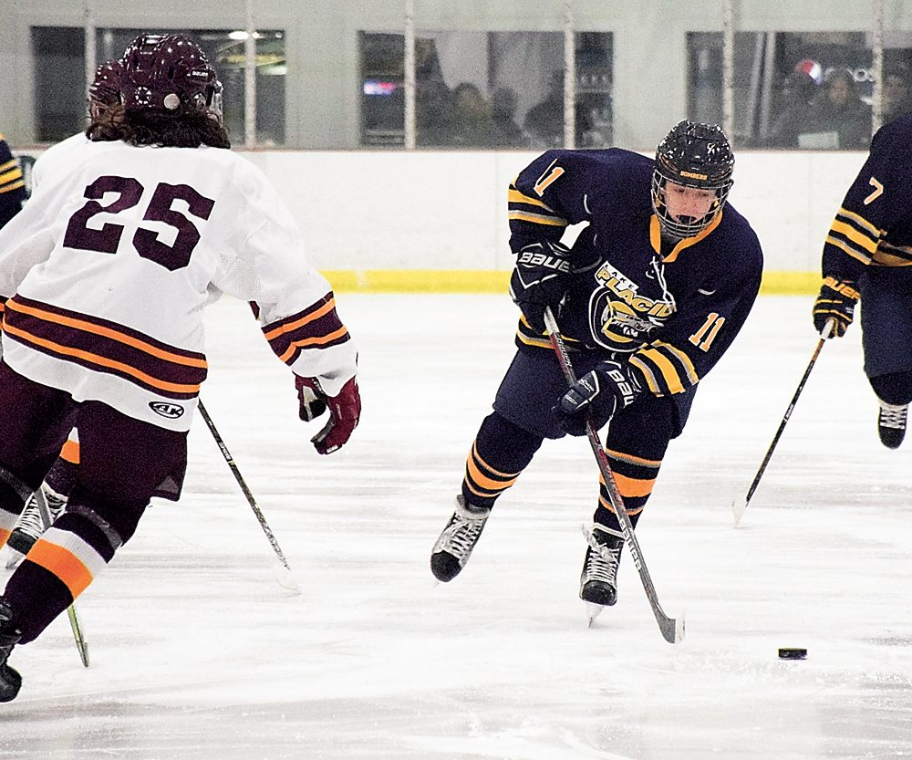 Lake Placid junior Cooper Holms moves the puck toward the Burnt Hills/Ballston Spa goal during the first period of Friday night's game. (Enterprise photo — Justin A. Levine)