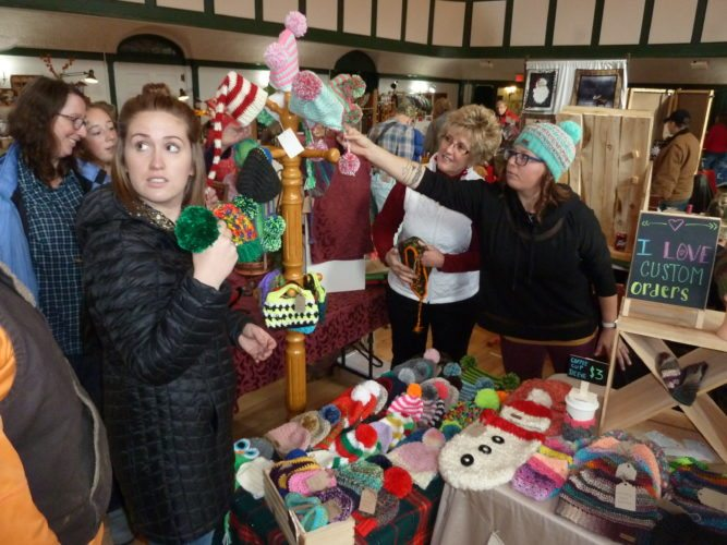 From left front, Kelsey Mathis buys winter hats from Sue Blanchard and Nikita McCormick of ADK Crochet at the Sparkle Village craft sale Saturday at the Harrietstown Town Hall in Saranac Lake. (Enterprise photo — Peter Crowley)
