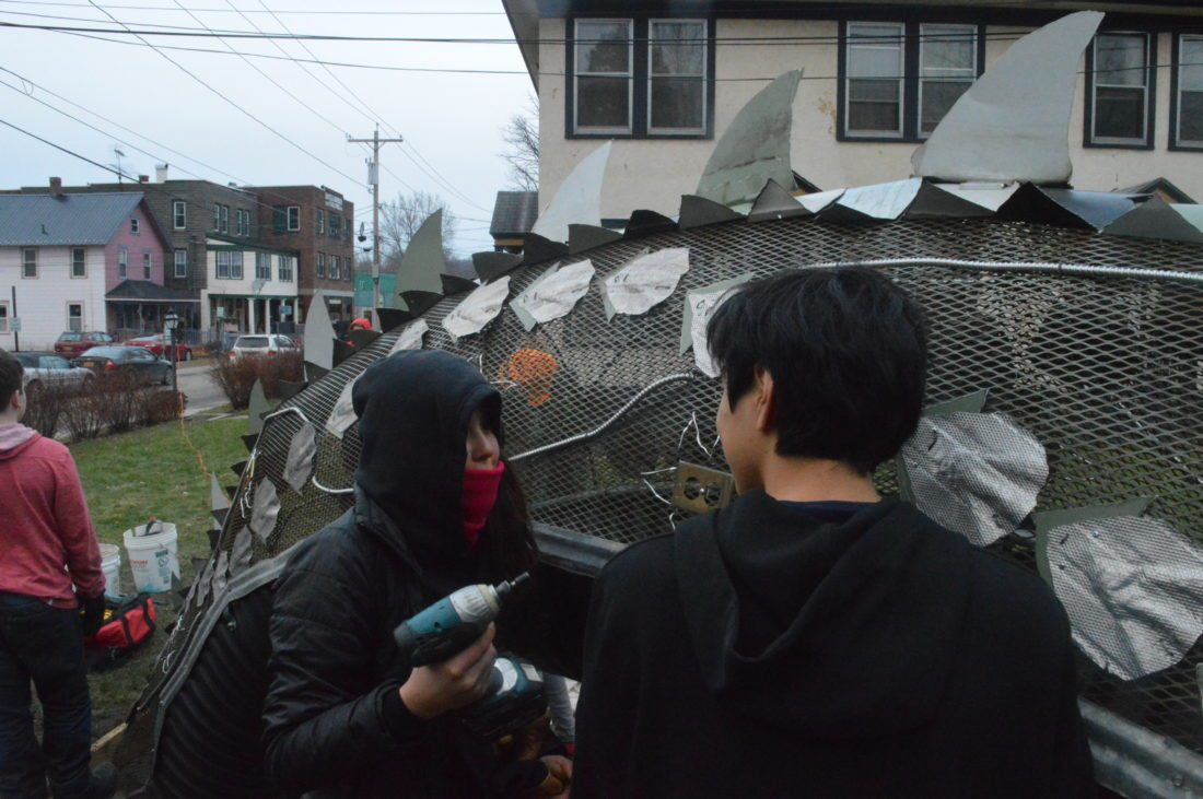 Romina and James, students at the North Country School, put the finishing touches on the midsection of their sea serpent made of recycled metal, which can be seen at 18-22 Woodruff St. in Saranac Lake. (Enterprise photo — Aaron Cerbone)