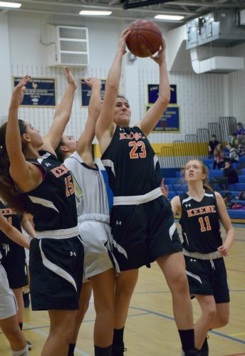 Keene's Elly Smith (23) grabs a rebound over Lake Placid's Lindsey Rath while Keene players Amelia Ellis (11) and Alyssa Summo (15) get in on the play Tuesday in Lake Placid. (Enterprise photo — Justin A. Levine)