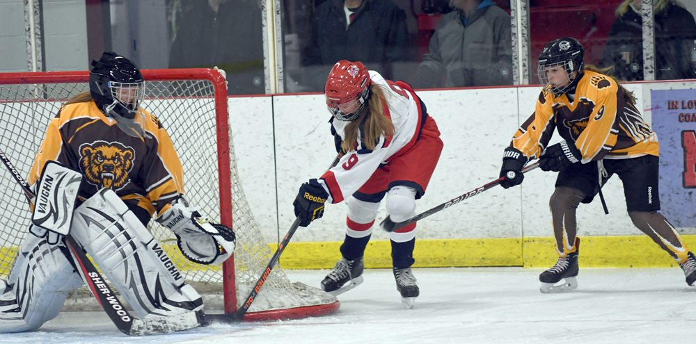 Lydia Bullock bangs a puck past Canton netminder Katie Weber during the third period for the fourth and final goal of Tuesday's game at the Saranac Lake Civic Center. Bullock scored twice in SLP's 4-0 victory. (Enterprise photo — Lou Reuter)