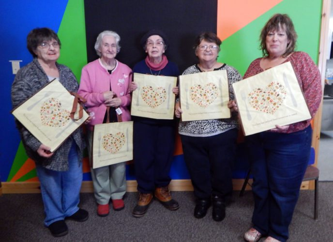 "Ladies from Adirondack Community Action Program's Senior Nutrition Site in Lake Placid display their new Hannaford's Bags 4 a Cause for the month of December. ACAP's Senior Nutrition Site was chosen to benefit from the sales of the bags for the month of November and December.  For every Hannaford's Fight Hunger Bags (the yellow bags which say, ""This bag has helped feed someone in need,"" on the front), the site will receive 25 cents. The more bags sold, the more the site will receive. Bags are available for purchase at Hannaford's in Lake Placid. (Photo provided)"