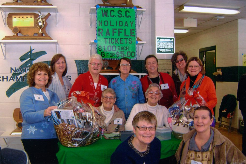 Women's College Scholarship Club members are shown with two holiday gift baskets. Back row from left are Beryl Szwed, Jill Zagrobelny, Elaine Holmlund, Deb Naybor, Heidi Gutersloh, Lynn Hidy and Linda Jackson. Seated at table, Linda Beairsto and Gloria Drucker. Front Susan Alexander and Stacy Cogan.  (Photo provided)