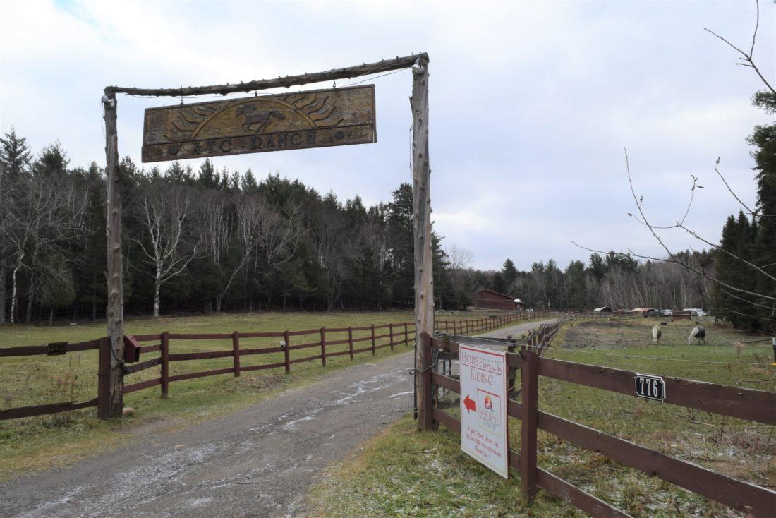 The gate at XTC Ranch in Lake Clear is open Wednesday after state police made an unexpected visit. The gate is often closed with a chain and padlock. Visitors are directed to call for admittance.  (Enterprise photo — Glynis Hart)