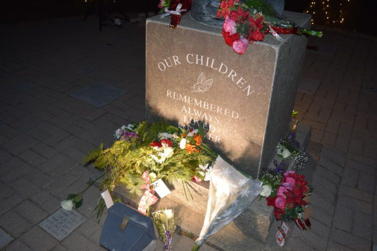 Flowers and evergreens are laid at the base of the Angel of Hope statue outside Adirondack Medical Center in Saranac Lake during Wednesday night's annual ceremony for bereaved parents. (Enterprise photo — Glynis Hart)