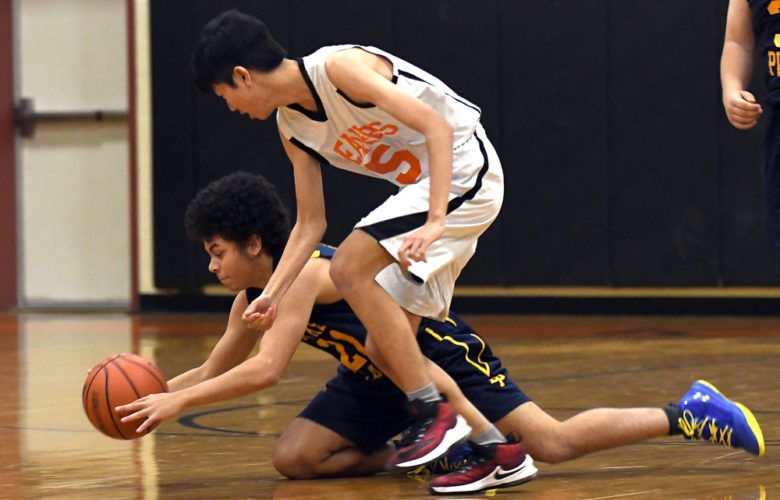 Lake Placid's Sean Ransom dives to the floor while chasing a loose ball with Keene's Ryo Kobayashi during the closing minutes of Thursday's matchup at the Beaver Dome in Keene Valley. (Enterprise photo — Lou Reuter)