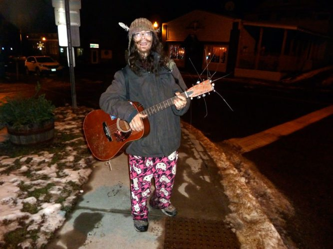 Rob Frost plays his 11-string guitar at the corner of Broadway and Bloomingdale Avenue in Saranac Lake on Nov. 28. (Enterprise photo — Peter Crowley)