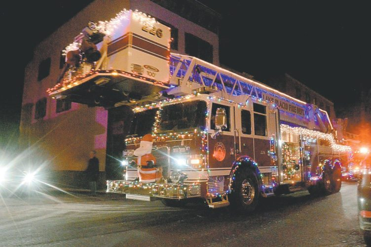 A Lake Placid fire engine rolls down Broadway in downtown Saranac Lake Friday evening as dozens of children and families watch Santa's Lighted Fire Truck Parade. (Enterprise photo — Aaron Cerbone)