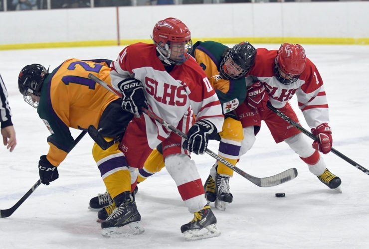 Saranac Lake's Ben Casagrain (11) and Dylan Amell tangle with two Guilderland opponents, including Evan Carey (12) following a faceoff during the third period of Saturday's game at the Saranac Lake Civic Center. (Enterprise photo — Lou Reuter)