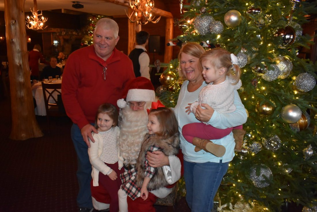 From left, Jerry Krug, Aubrey Trudeau, Ava Krug, Laurie Krug and Hadley Trudeau pose with Santa at the Mirror Lake Inn during the Holiday Village Stroll in LakePlacid. (Enterprise photo —Glynis Hart)