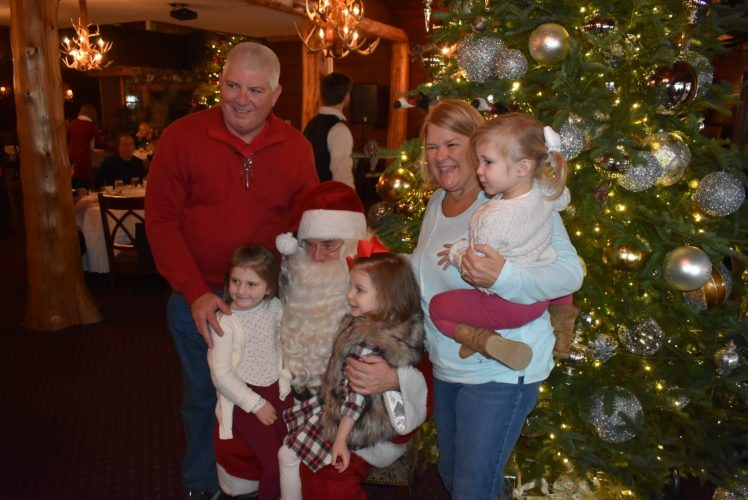 From left, Jerry Krug, Aubrey Trudeau, Ava Krug, Laurie Krug and Hadley Trudeau pose with Santa at the Mirror Lake Inn during the Holiday Village Stroll in Lake Placid. (Enterprise photo — Glynis Hart)