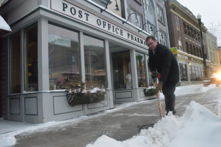 Jim Bevilacqua, owner of the Post Office Pharmacy in Saranac Lake, shovels the sidewalk in front of his Main Street store this morning, on the second day of consistent snow expected to last through Wednesday. (Enterprise photo — Aaron Cerbone)