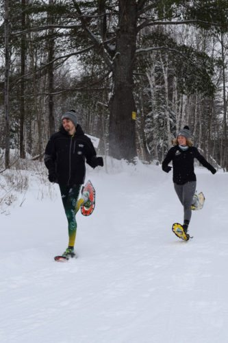 Paul Smith's College snowshoe racers Joseph St. Cyr and Chloe Matillio test out the trails at Dewey Mountain Recreation Center in Saranac Lake Feb. 16, 2017 in preparation for the World Snowshoe Championships.  (Enterprise photo — Chris Knight)
