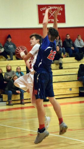 Saranac Lake senior Emery Swanson drives to the basket around AuSable Valley's Carter Matzel during the first half of the Red Storm's home loss Wednesday night. (Enterprise photo — Justin A. Levine)