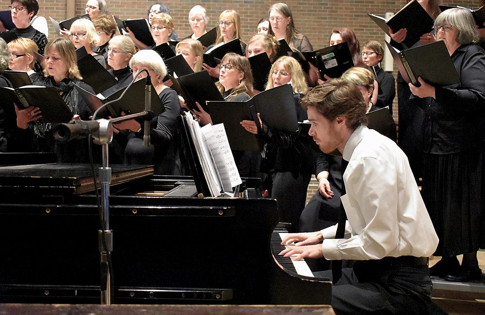 """Drew Benware plays piano during the Northern Lights Choir's winter concert at St. Bernard's Church in Saranac Lake. The crowd erupted in ceremonious applause after his rendition of Joseph Haydn's """"The Heavens Are Telling."""" (Enterprise photo — Griffin Kelly)"""
