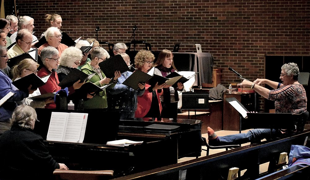 """Karen Butters conducts the Adirondack Singers at St. Bernard's Church in Saranac Lake with her leg propped on a chair. """"I've got two arms; I don't need legs to conduct,"""" she said. (Enterprise photo — Griffin Kelly)"""