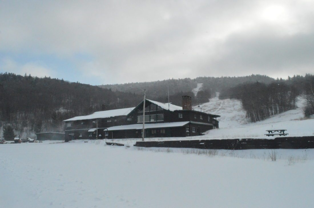 Big Tupper Ski Area's main lodge sits dormant this winter with the trails of Chair 1 behind it. The ski center is scheduled to reopen for the 2018-19 season. (Enterprise photo — Aaron Cerbone)