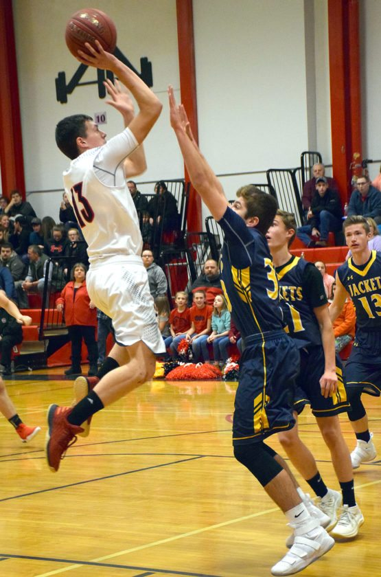 Tupper Lake's Kameron Sarvis takes a jump shot over Madrid-Waddington's Peyton Chambers during the second quarter of Monday's game in Tupper Lake. (Enterprise photo — Justin A. Levine)