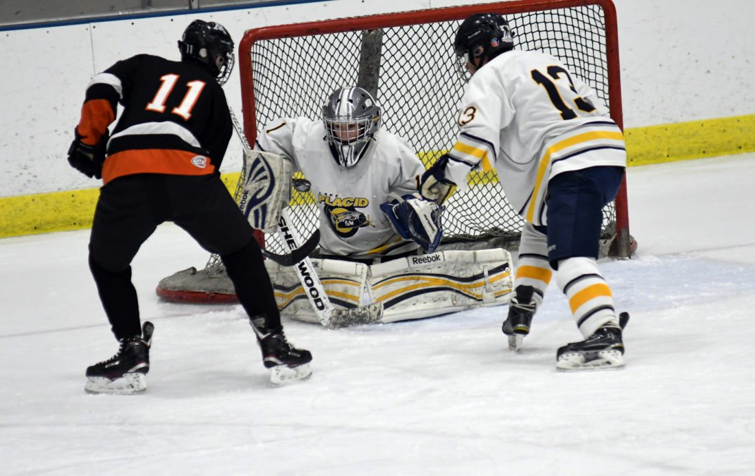 Lake Placid goalie Anders Stanton stops a shot by Middlebury's Kamrin Bartlett while Jarrett Hathaway defends for the Blue Bombers during the opening period of Tuesday's game. (Enterprise photo — Lou Reuter)