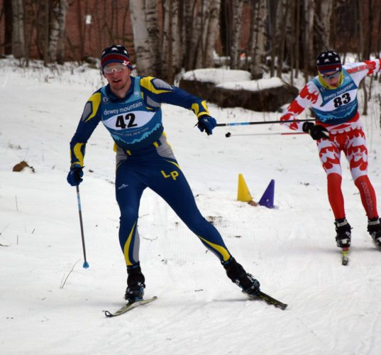 Lake Placid's Scott Schulz, followed by Saranac Lake's Lauchlan Cheney-Seymour, nears the finish line of the first nordic ski race of the season Wednesday at Dewey Mountain in Saranac Lake. (Enterprise photo — Justin A. Levine)
