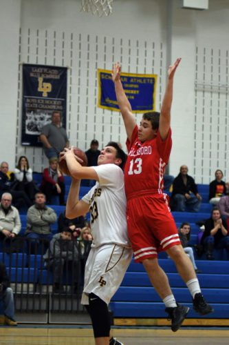 Lake Placid's Jake Coursen attempts to get off a shot despite being fouled by Willsboro's Oliver Lee during Wednesday's varsity hoops contest in the Blue Bombers' gym. Lake Placid trailed 21-12 at the half and nearly pulled out the victory before falling to the Warriors 39-35. (Enterprise photo — Lou Reuter)