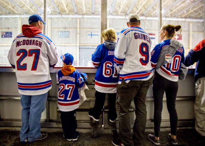 Matt Theis (wearing the No. 9 jersey), his 8-year-old twin sons Ryan (27) and Brandon (61), and others watch the New York Rangers hockey team practice at Lake Placid's Olympic Center in October. (Photo provided — Elise Ruocco, Olympic Regional Development Authority)