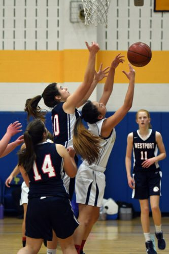 Laurel Miller of Lake Placid and Westport's Hannah Schwoebel of Westport battle for a rebound during Thursday's game. Also pictured for Westport are Abby Mero (14) and Rachel Storey. (Enterprise photo — Lou Reuter)