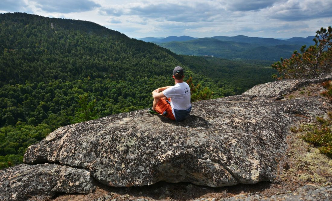 A hiker takes in the view from the summit of Huckleberry Mountain in Warren County. The Open Space Institute recently purchased more than 1,000 acres that includes the mountain, which will likely be added to the state's Forest Preserve. (Photo provided)