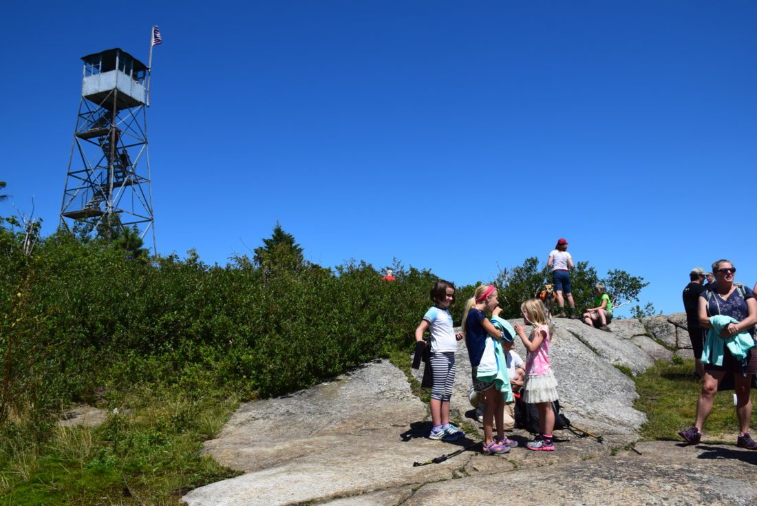 Several dozen people gathered at the summit of Poke-O-Moonshine Mountain in July for the 100th anniversary of the fire tower there. The Aeromotor tower was installed in 1917, and is just one of many fire towers that have been restored for use by the public. (Enterprise photo — Justin A. Levine)
