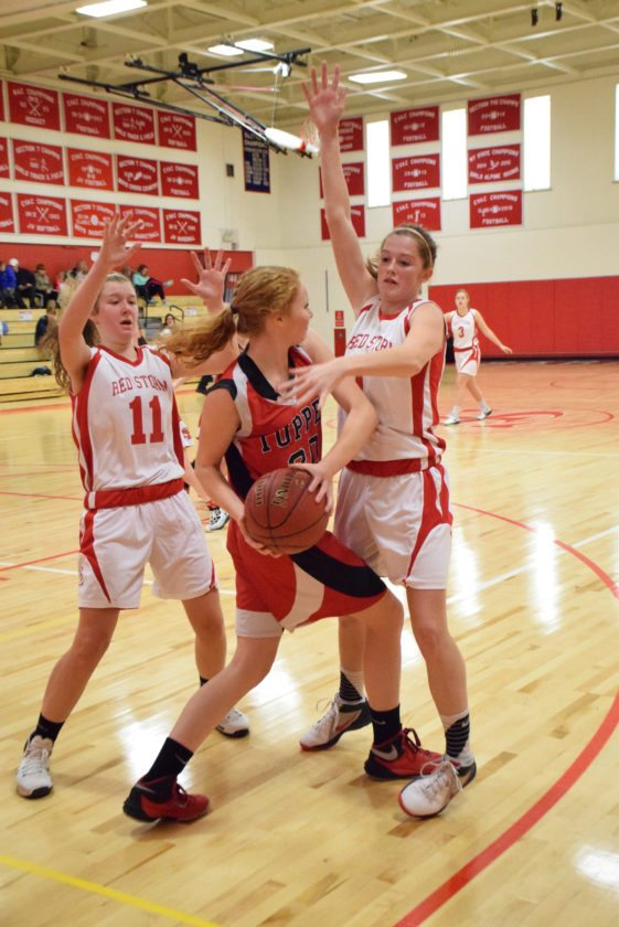 Tupper Lake's Sophia Martin looks for an outlet for the ball as Saranac Lake defenders Roslyn McClatchie (11) and Kylee Clark smother her during the first half of the non-league game in Saranac Lake Wednesday afternoon. The Red Storm went on to win the game.  (Enterprise photo — Justin A. Levine