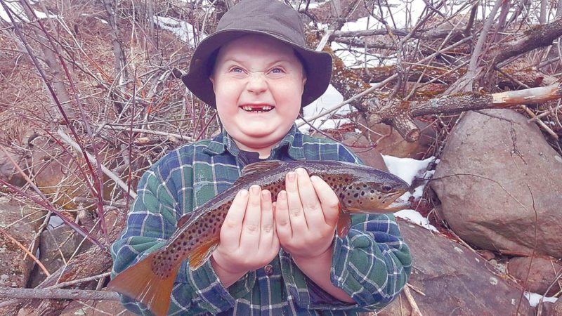 Lucas Rogers, 8, of Saranac Lake, smiles as he holds a brown trout he caught April 2 in the Chubb River in Lake Placid. Trout season opened April 1 in New York state, but ice still covered many waterways and few anglers seemed to be out that day. (Photo provided — Brett Rogers)