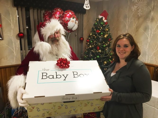 Santa Claus presents a baby box to Jennifer LaDue Ball, who is expecting a baby boy in March, at Adirondack Medical Center in Saranac Lake. (Photo provided)