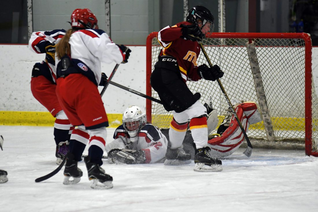 SaranacLake Placid goaltender Whitney Battistoni smothers the puck in a spray of ice while Ithaca's Shea Baker applies pressure and SLP players, including Lydia Bullock (9) close in to defend the play during the second period of Thursday's game.   (Enteprise photo — Lou Reuter)