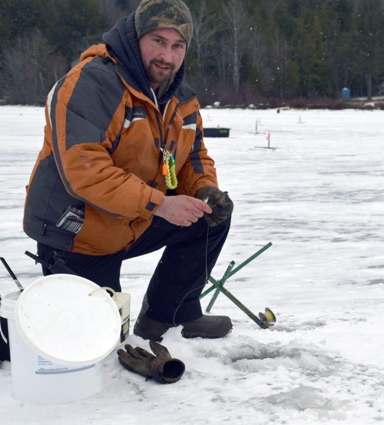 Mike Archer of the Rome, New York, area checks one of his tip-ups at the Northern Challenge ice fishing derby in Tupper Lake in February 2016. (Enterprise photo — Justin A. Levine)