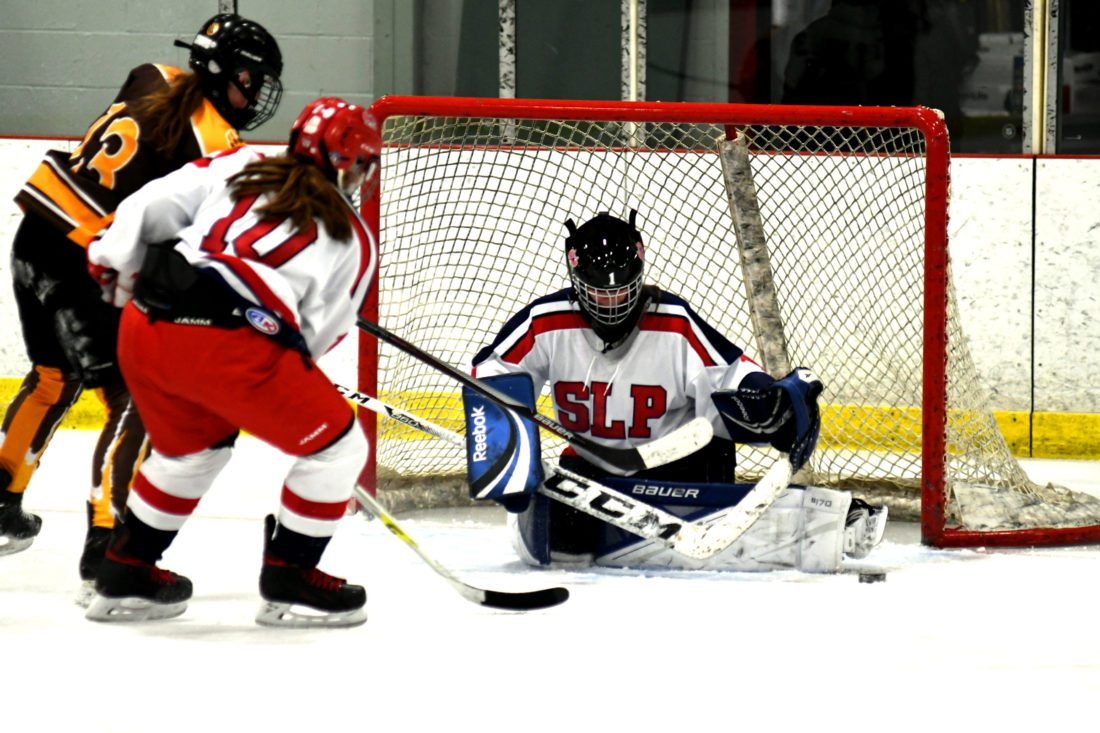 Saranac Lake Placid goalie Brooke Paries steers the puck away from the net while teammate Madelyn Gay defends and Lizzy Christy pressures the net for Canton. (Enterprise photo — Lou Reuter)