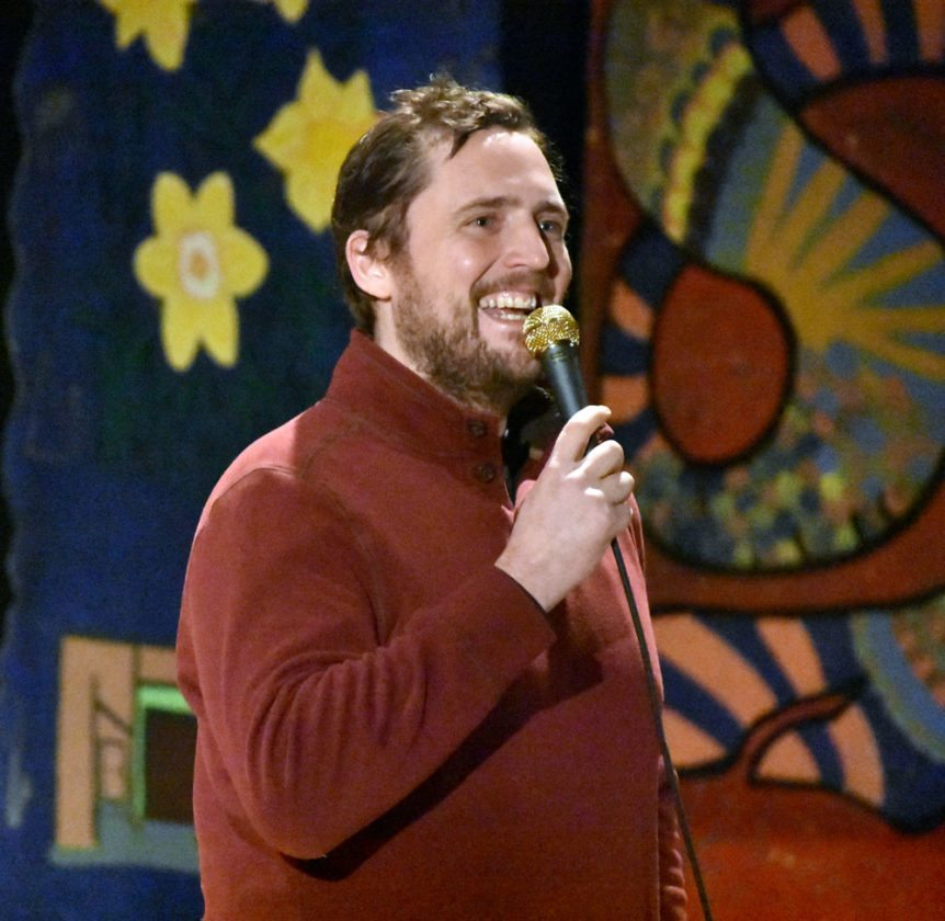 Comedian and Saranac Lake resident Owen Benjamin pokes fun at the cold weather in the Adirondacks Sunday night at Harrietstown Town Hall during First Night Saranac Lake. (Enterprise photo — Griffin Kelly)