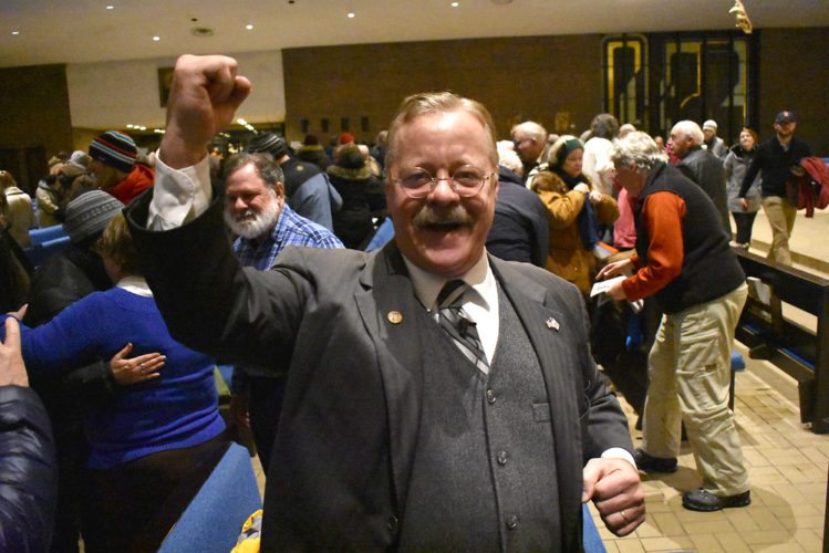 Joe Wiegand, impersonating President Theodore Roosevelt, pumps his fist after delivering an informative and encouraging speech to audiences at St. Bernard's Church Sunday night during First Night Saranac Lake. (Enterprise photo — Griffin Kelly)