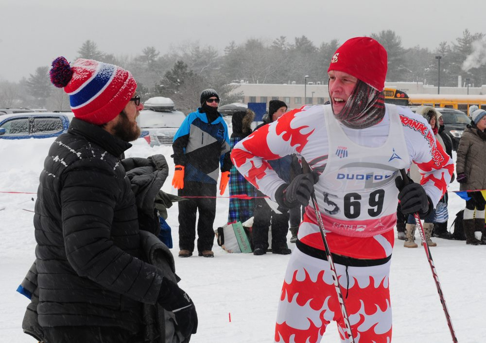 Amid frigid temperatures, Saranac Lake nordic ski coach Keith Kogut brings a coat to Jacob Alberga after Alberga anchored Saranac Lake's lead varsity boys team to a third-place finish in a cross-country ski relay race Saturday in Queensbury. (Enterprise photo — Peter Crowley)