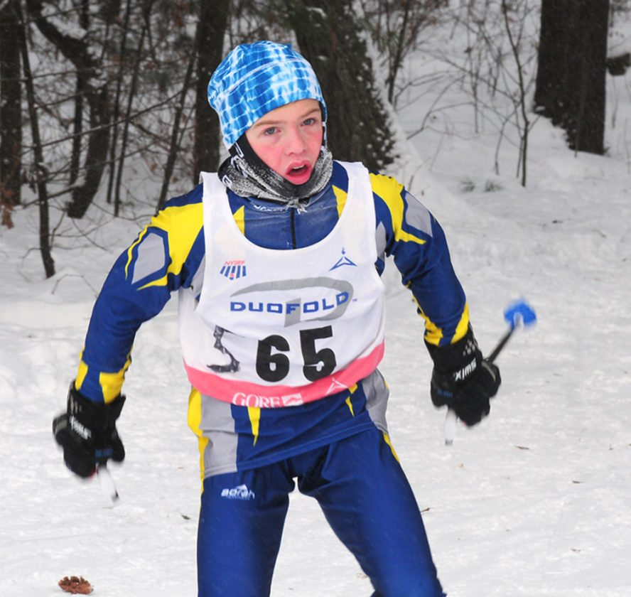 Lake Placid's Tate Franz comes out of the woods in the boys varsity cross-country ski relay race Saturday in Queensbury. (Enterprise photo — Peter Crowley)