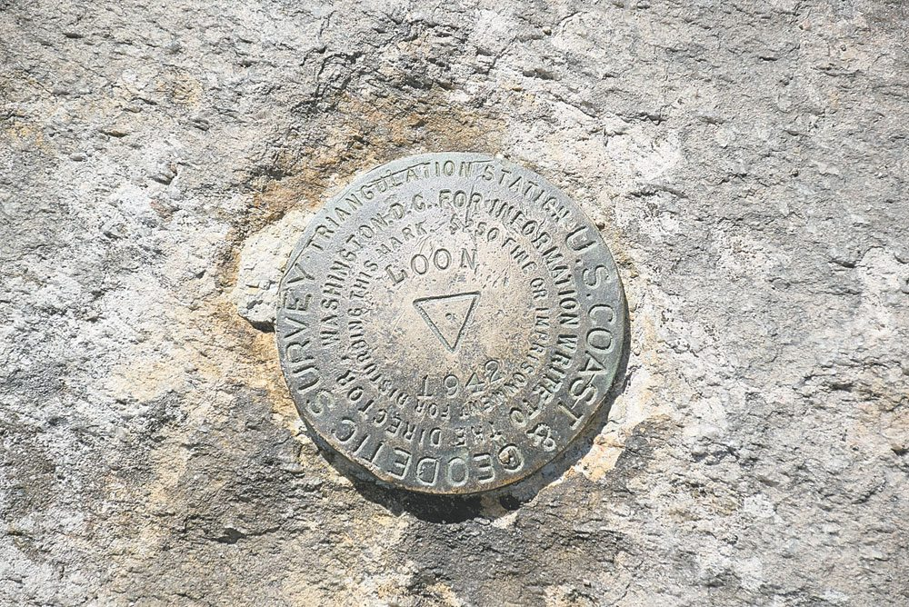 A new hiking challenge that can be worked on anywhere in the country asks hikers to document U.S. benchmarks, like the one seen here at the summit of Loon Lake Mountain. (Enterprise photo — Justin A. Levine)